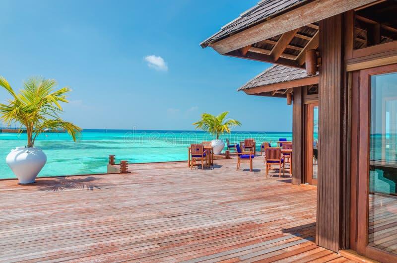 Innaffi il ristorante ai precedenti del cielo blu nell'isola delle Maldive fotografie stock libere da diritti