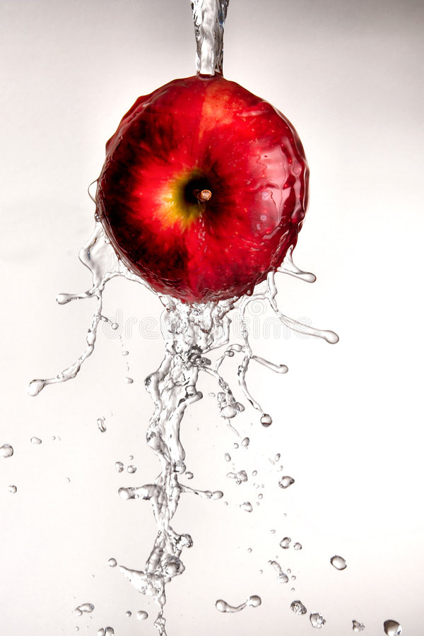 Innaffi il versamento fuori dalla mela rossa. fotografia stock