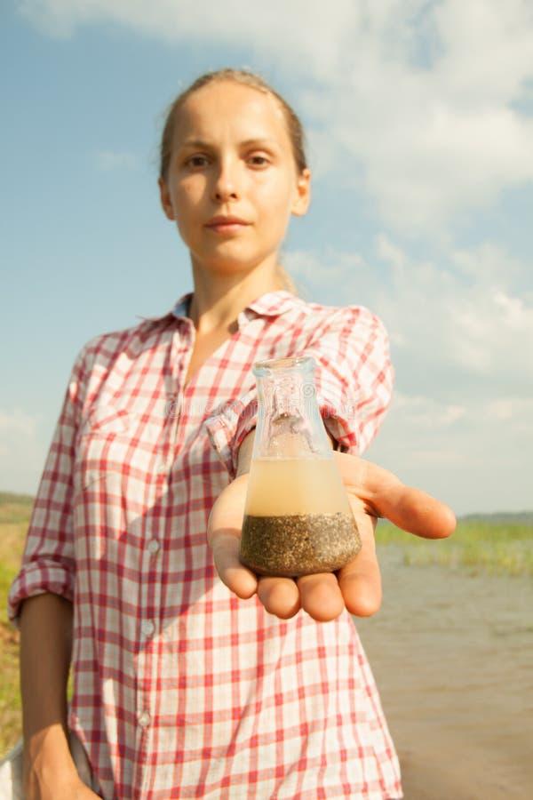 Innaffi la boccetta chimica della tenuta della donna della prova della purezza con acqua, il lago o il fiume nei precedenti fotografie stock libere da diritti