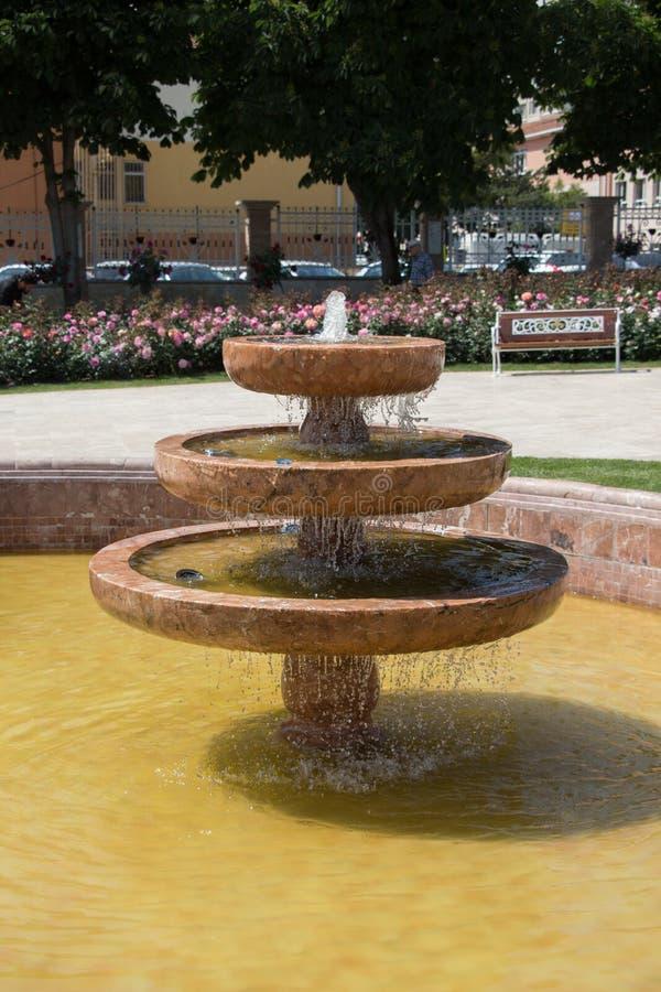 Innaffi lo zampillo fuori dalla fontana nel giardino immagine stock