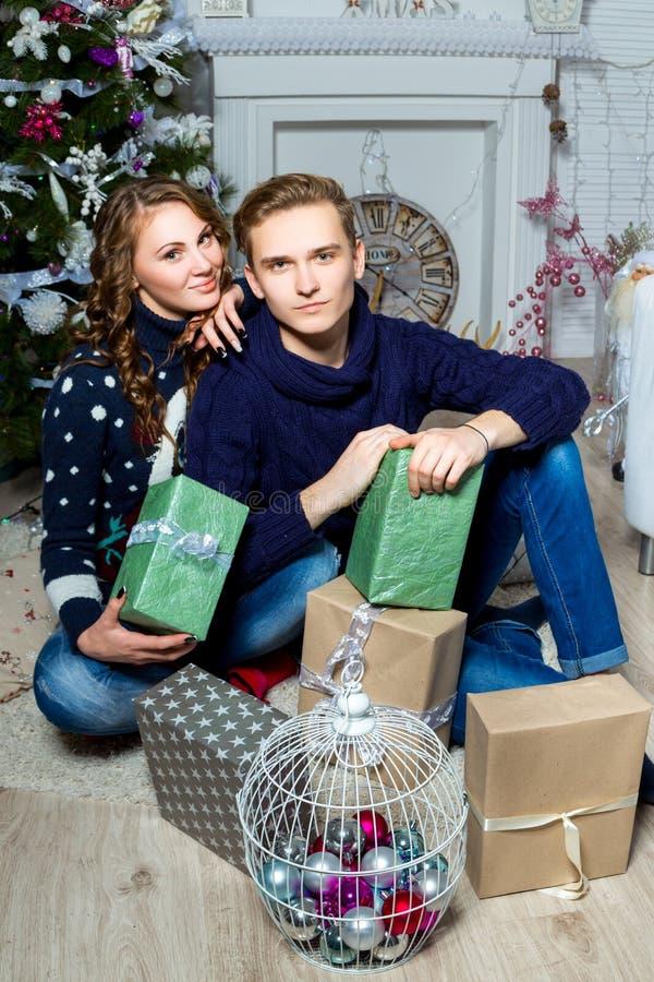 Innamorarsi ragazzo e ragazza che si siedono vicino all'albero di Natale i immagini stock libere da diritti