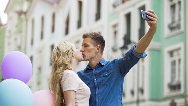 Innamorati che baciano davanti alla macchina fotografica dello smartphone che prende selfie romantico alla data fotografie stock libere da diritti