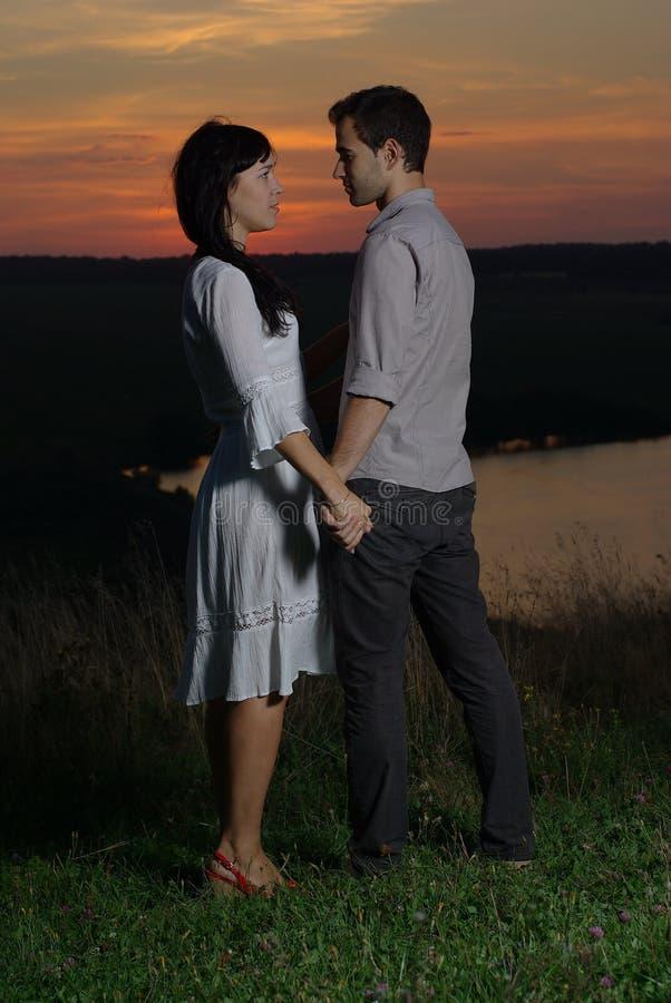 Innamorati nel tramonto e nel lago fotografie stock libere da diritti