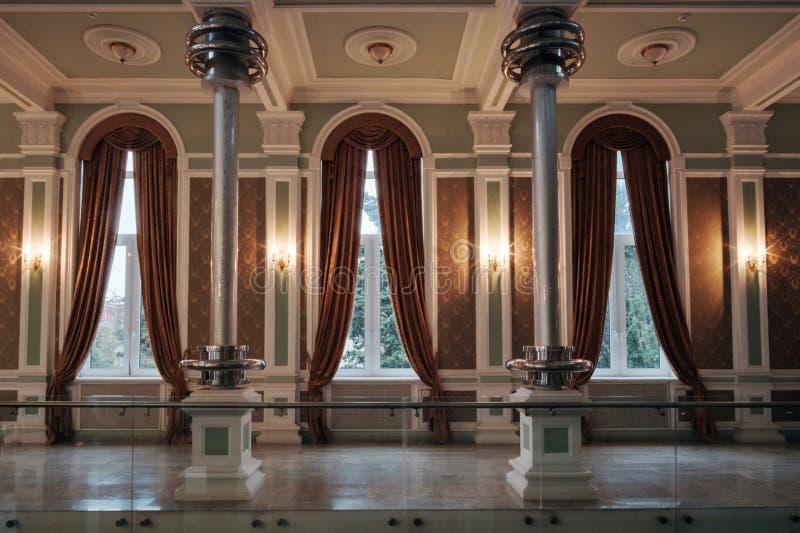 Innanför ett klassiskt rum med fönster och veterangardiner royaltyfri foto