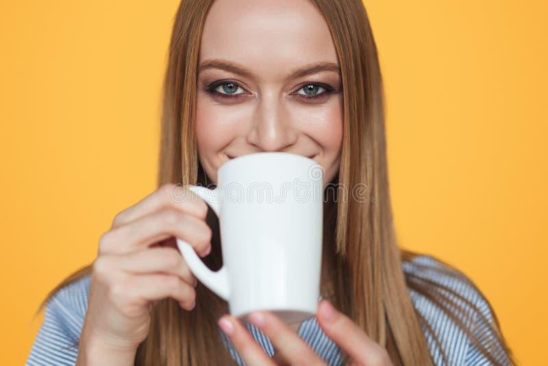Innehåll av kvinnan som dricker kaffe på apelsinen fotografering för bildbyråer