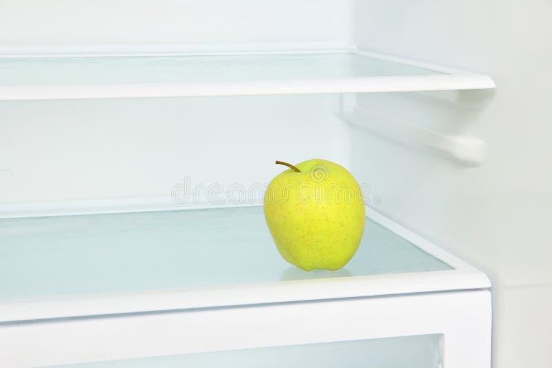 Innehåll lutning- och urklippmaskeringen Gult äpple i det inhemska kylskåpet som tas clo royaltyfria foton