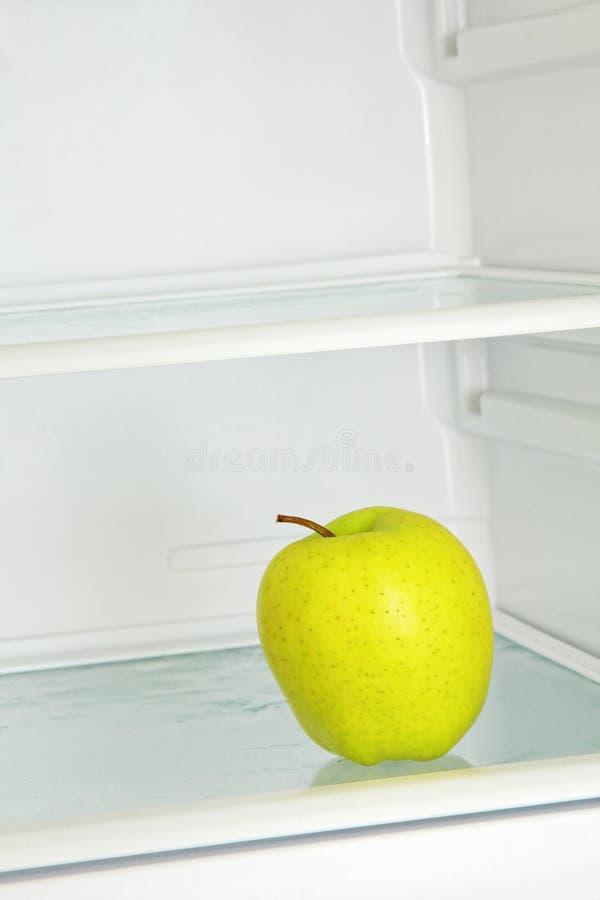 Innehåll lutning- och urklippmaskeringen Gult äpple i inhemskt kylskåp royaltyfria bilder