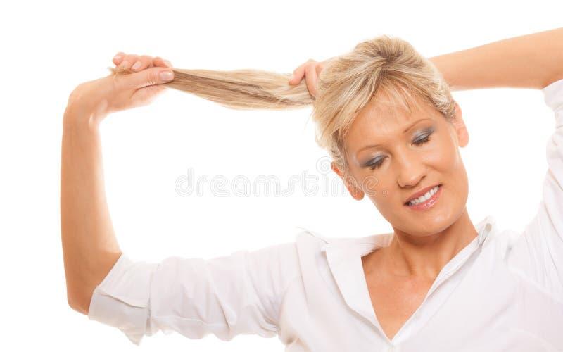 Innehav för mogen kvinna för stående blont hennes långa hår arkivfoton