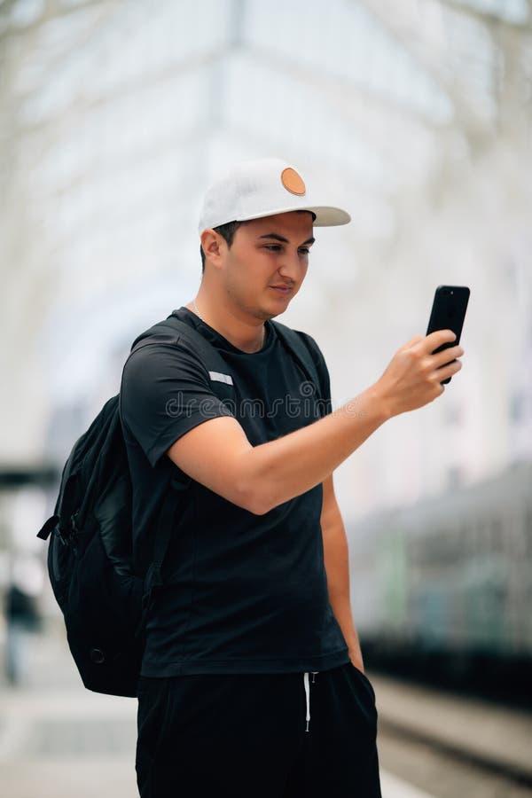 Innehav för ung man genom att använda telefonen med ryggsäckanseende på plattformen på drevstationen Loppbegrepp, kopieringsutrym arkivfoton