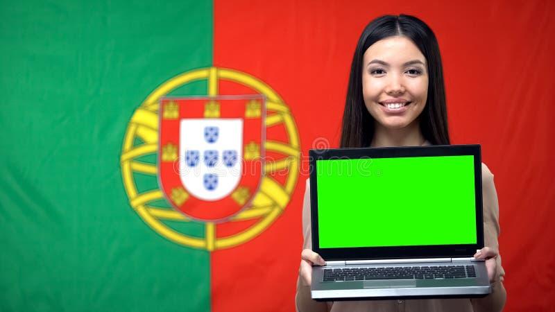 Innehavbärbar dator för kvinnlig student med den gröna skärmen, portugisisk flagga på bakgrund royaltyfria bilder