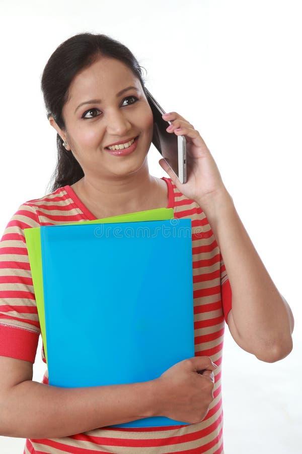 Innehavet för den unga kvinnan bokar och tala på mobiltelefonen arkivfoto