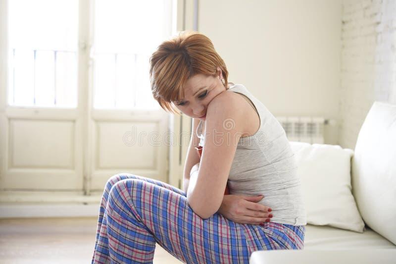 Innehavet för den unga kvinnan som gör ont krampen för buklidandemagen, och perioden smärtar fotografering för bildbyråer