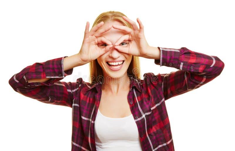 Innehavfingrar för ung kvinna framme av hennes ögon royaltyfri foto