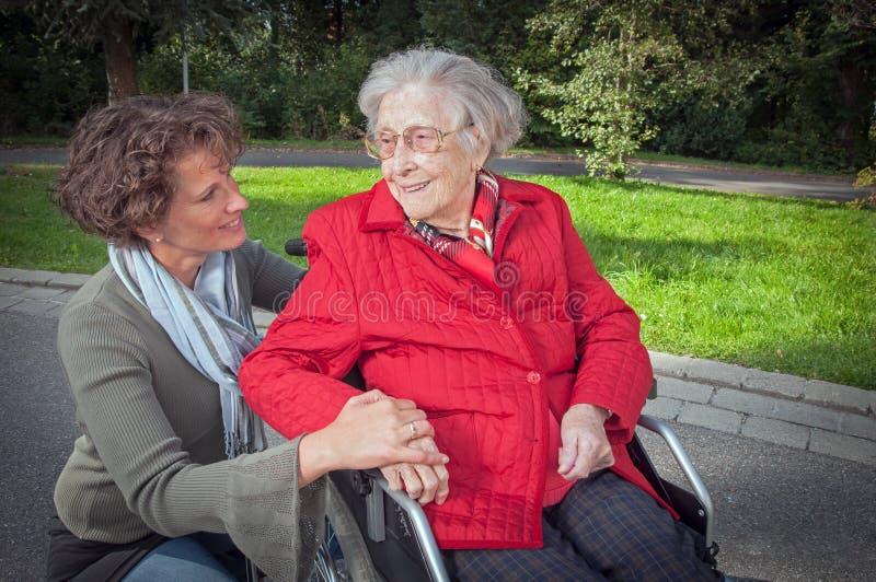 Innehavhand för ung kvinna av den gamla damen som sitter i rullstol fotografering för bildbyråer