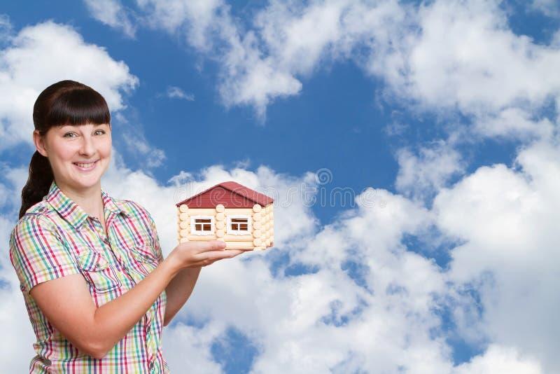 Innehavhem för ung kvinna på en bakgrund av himmel arkivbild