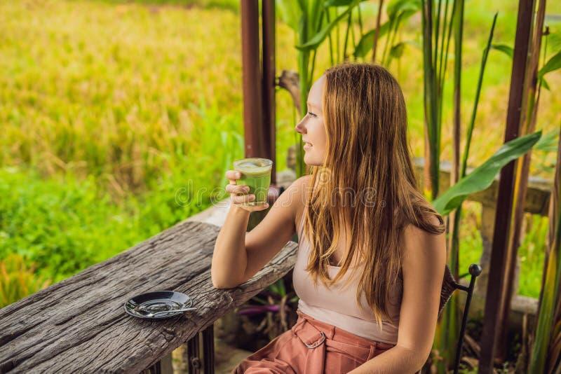 Innehavkopp för ung kvinna av matchaLatte, grönt te, på den gamla träbakgrundstabellen arkivfoto