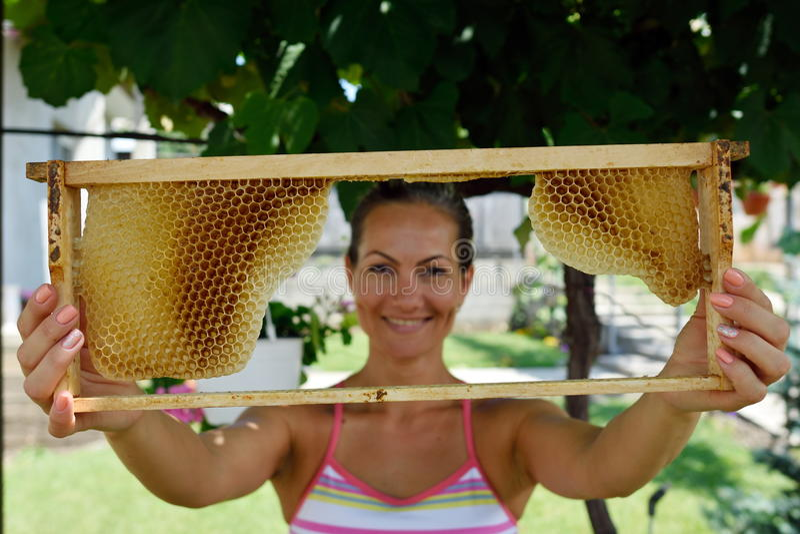 Innehavram för ung kvinna med honungskakan arkivfoto