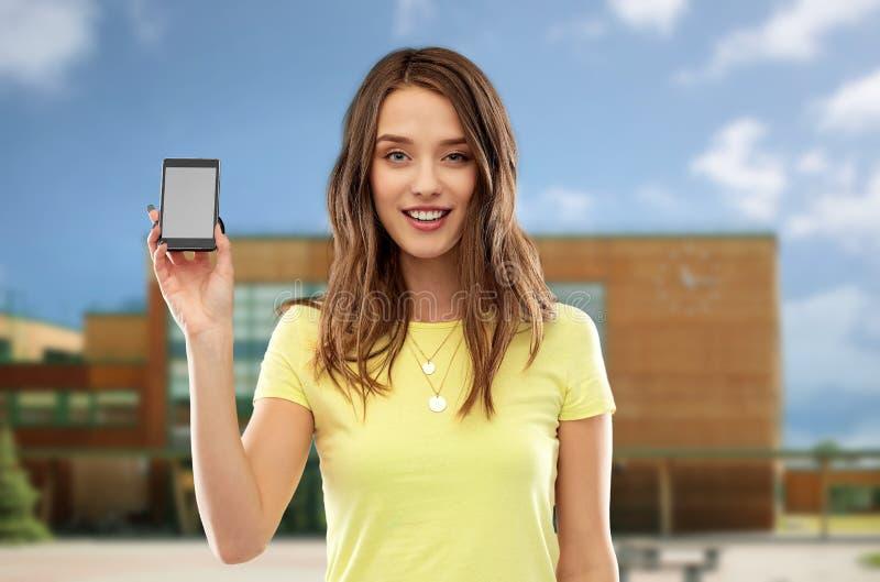 Innehavsmartphone för tonårs- flicka över skola arkivfoto