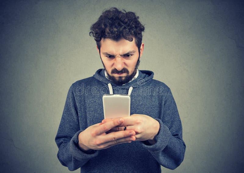 Innehavsmartphone för ung man som är uppriven med textmeddelandet royaltyfri fotografi