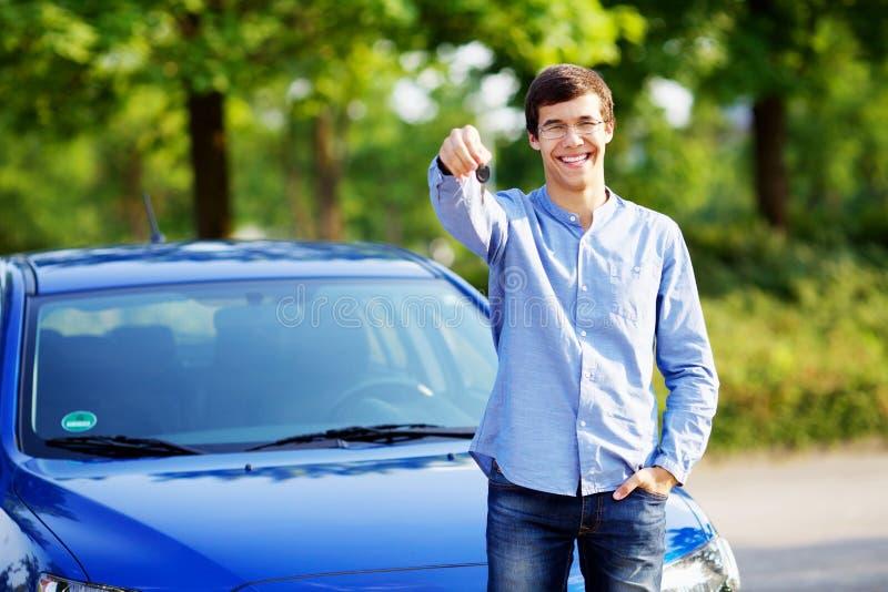 Innehavtangent för ung man av hans nya bil arkivfoto