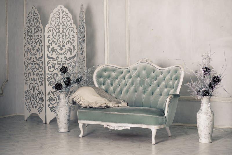 Innen mit Weinlesemöbeln, Retro- schönes graues Sofa Weißer Wohnzimmerinnenraum Große antike Boden-Vasen mit stockbild
