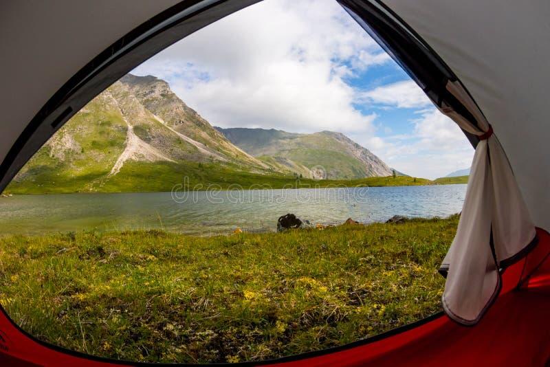 Innenansicht das Zelt aus den Bergen heraus und See im Sommer stockfotografie