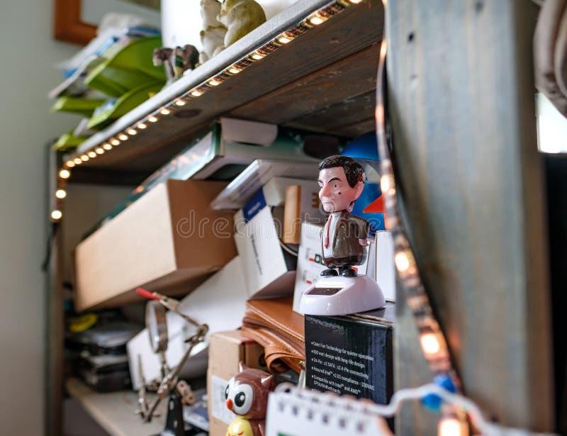 Innenansicht einer Büroarbeitsplatz-Vertretungsunordnung, wie auf einem hölzernen Bücherregal gesehen lizenzfreies stockbild