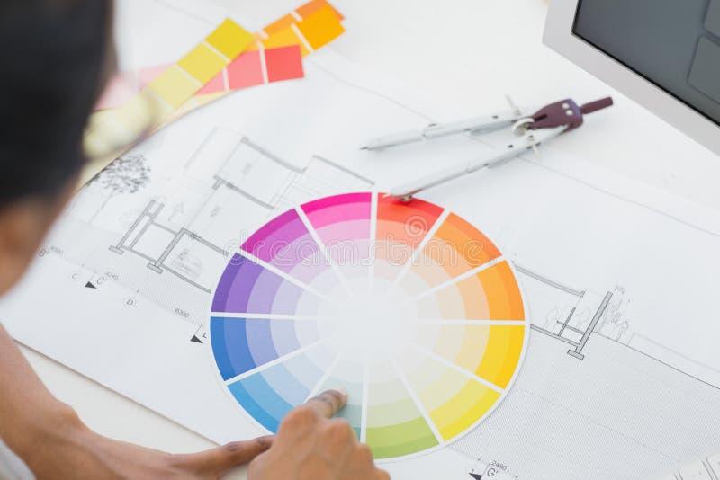 Innenarchitekt, der Farbrad auf Schreibtisch betrachtet stockfoto