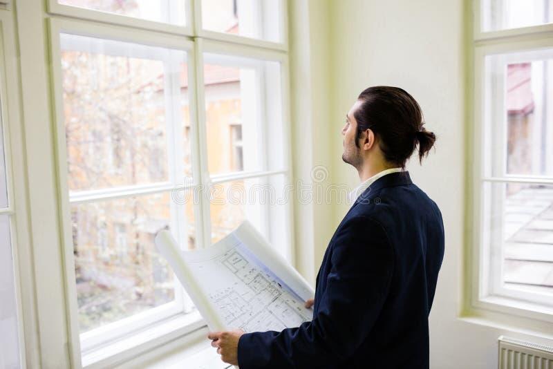 Innenarchitekt mit dem Plan, der zwar Fenster schaut stockbild