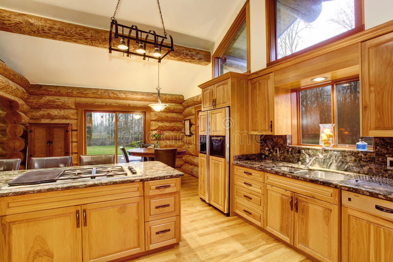 Innenarchitektur der Blockhausküche mit Honigfarbkabinetten stockbilder