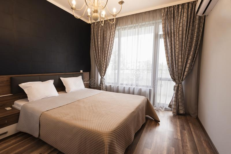 Innenarchitektur des modernen Schlafzimmers Luxusbettraum mit braunem Farbton Windows mit langen Vorhängen und Scheren stockfotografie