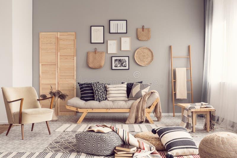 Innenarchitektur des stilvollen Wohnzimmers mit skandinavischem Sofa, grauer Wand und nat?rlichen Akzenten lizenzfreie stockfotos