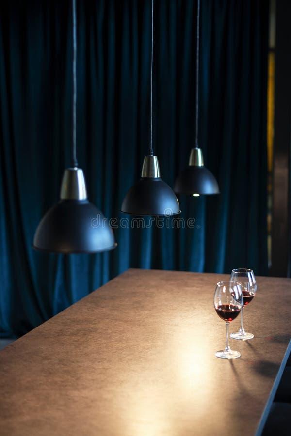 Innenarchitektur eines Restaurants oder des Cafés Ein Seitenfoto eines Holztischs mit zwei Gläsern Rotwein, Überhängen drei schwa stockbild