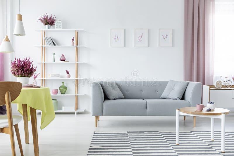 Innenarchitektur mit bequemer skandinavischer Couch, hölzernem Couchtisch, gestreifter Wolldecke und Grafiken auf dem Boden, wirk lizenzfreie stockbilder