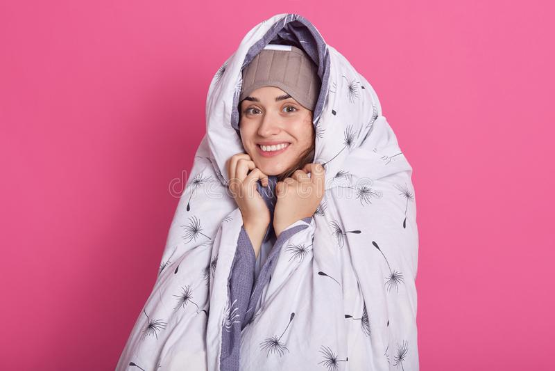 Innenatelieraufnahme der lächelnden netten attraktiven weiblichen Stellung über rosa Hintergrund, versteckend unter der Decke und stockbild