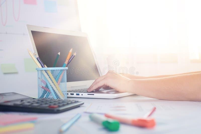 Innenbild der Person, die auf dem Laptop arbeitet, mit Rechenmaschine, Schreibstiften auf dem Tisch, komfortabler Arbeitsbereich, stockfotos