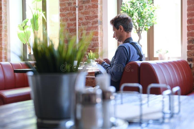 Innencaf?tabellen und -st?hle Mannphotograph, der am Tisch sitzt St Petersburg Russland 06 02 2019 lizenzfreies stockbild