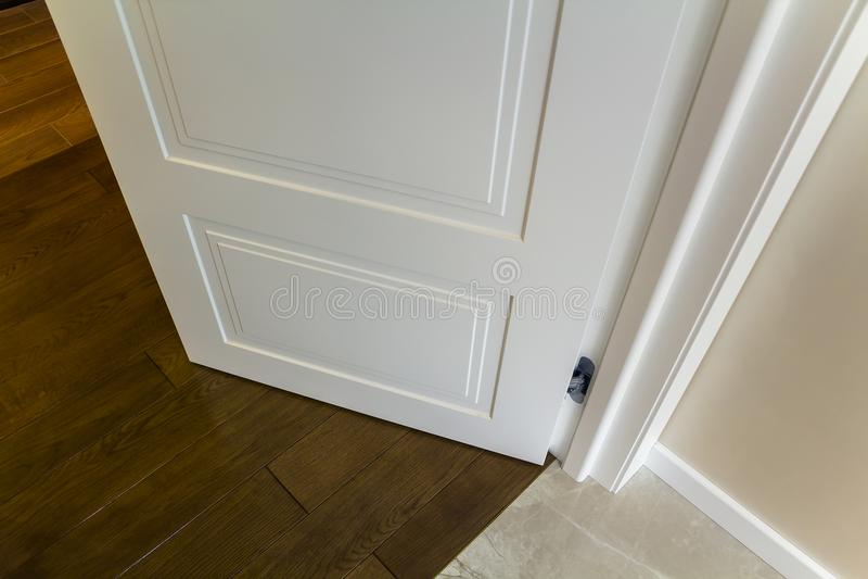 Innendetail des modernen Hauses mit hölzernem Parkettboden und weißer Tür Wohnung nach Erneuerungsnahaufnahme stockfotografie