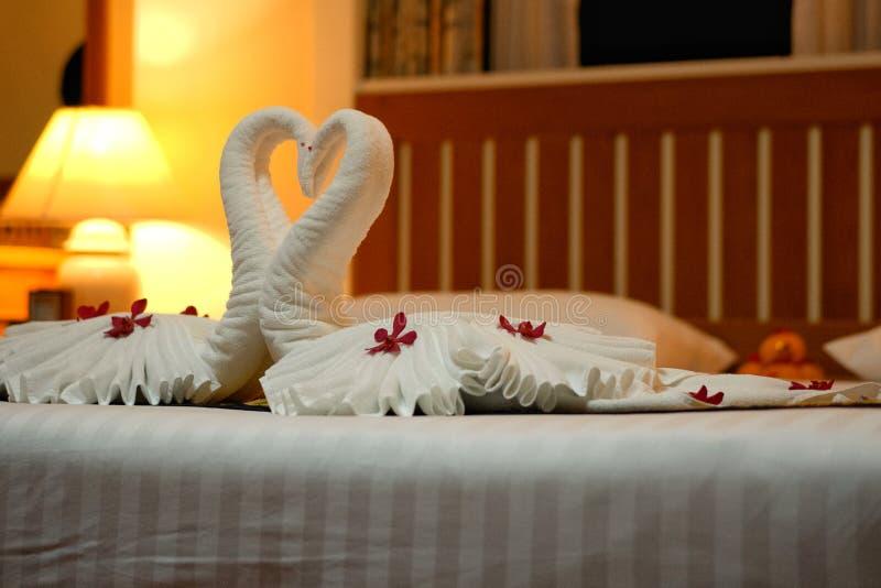 Inneneinrichtung des modernen Schlafzimmers auf weißer Decke und hölzernem Bett für Flitterwochen lizenzfreie stockbilder