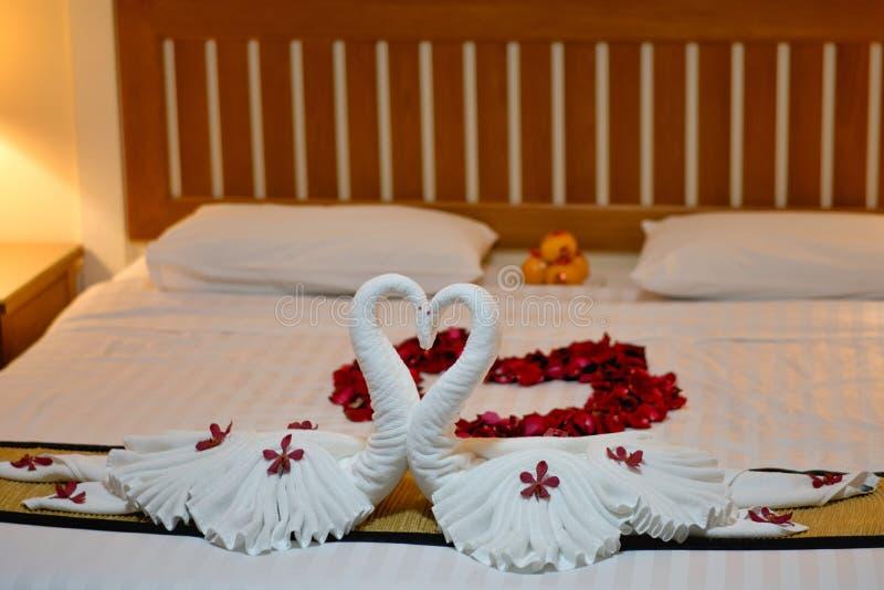 Inneneinrichtung des modernen Schlafzimmers auf weißer Decke und hölzernem Bett für Flitterwochen stockbild