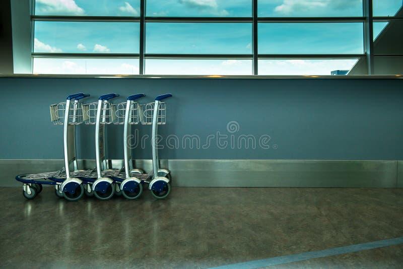 Innenflughafengepäckwarenkorb oder Laufkatze des Abfahrtaufenthaltsraums am Flughafen stockbild
