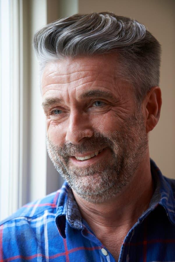 Innenhaupt- und Schulter-Porträt des lächelnden reifen Mannes stockbilder