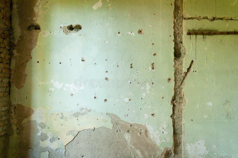 Innenhausmauergips mit Einschusslöchern und Schaden vom Schrapnell von der Granate lizenzfreies stockbild