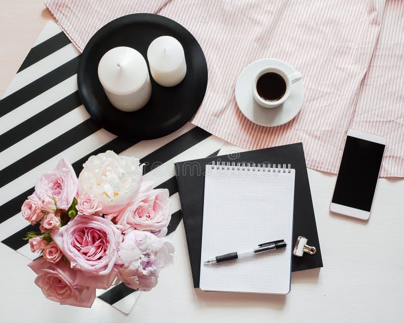 Innenministerium-Arbeitsplatz Notizbuch mit copyspace Schönheitsblog Frauenmode-accessoires, -telefon und -kaffee auf weißem Bett lizenzfreie stockfotografie