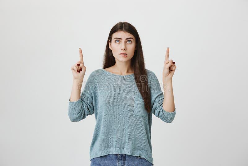 Innenporträt der heißen kaukasischen Frau mit dem langen Haar, oben zeigend und schauen und drücken Wunsch durch das Beißen von L stockfoto