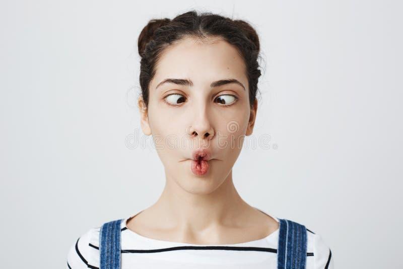 Innenporträt der lustigen kindischen Frau, die Fischlippen herstellt und mit verrückten Augen ihr betrachtet, durchbohrte die Nas stockfoto