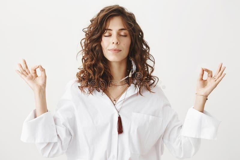 Innenporträt der ruhigen schönen kaukasischen Frau, die in der weißen Bluse, lächelnd beim Anheben von Händen mit Zen meditiert stockbild