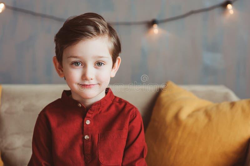 Innenporträt des glücklichen hübschen stilvollen Kinderjungen, der auf gemütlicher Couch sitzt lizenzfreies stockfoto