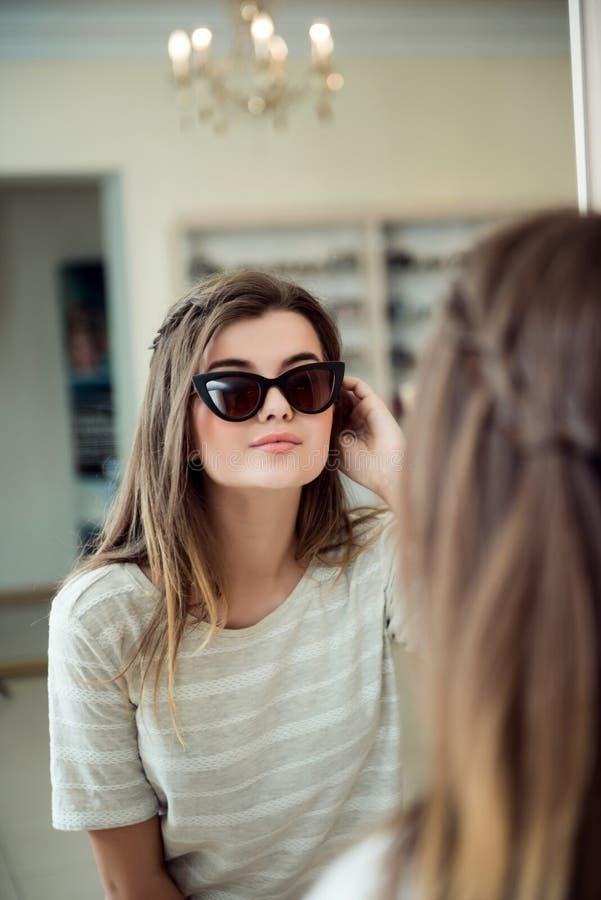 Innenporträt des modernen kaukasischen Brunette, der in Richtung zum Spiegel beim Handeln des Einkaufs im Optikerspeicher, wählen stockfotografie