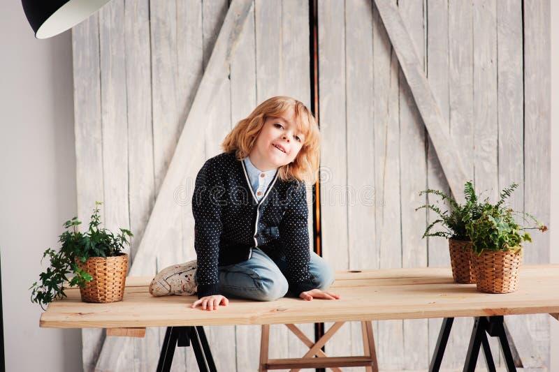 Innenporträt von 5 Jahren alten Jungen mit dem langen Haar, das auf Tabelle sitzt stockbild